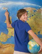Teenage boy with globe, smiling, portrait - stock photo