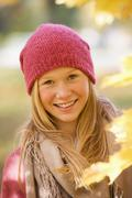 Austria, Close up of teenage girl with maple leaf, smiling - stock photo