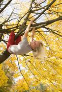 Stock Photo of Austria, Young woman hanging on maple tree in autumn