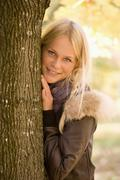 Stock Photo of Austria, Young woman standing besides maple tree in autumn