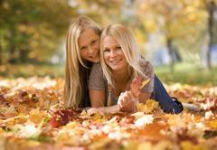 Stock Photo of Austria, Sisters lying on autumn leaf, smiling, portrait