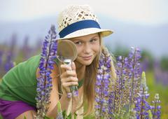 Austria, Teenage girl looking at lupine through magnifying glass - stock photo