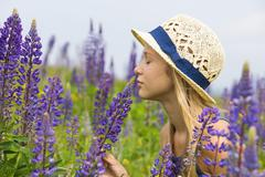 Stock Photo of Austria, Teenage girl smelling lupine flower