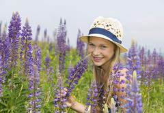 Stock Photo of Austria, Teenage girl holding lupine flower, smiling, portrait