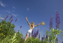 Austria, Teenage girl standing in lupine field Stock Photos