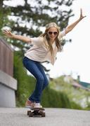 Austria, Teenage girl doing skateboarding - stock photo
