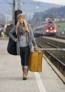 Stock Photo of Austria, Teenage girl with suitcase on train station
