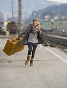 Austria, Teenage girl running on train station with suitcase Stock Photos