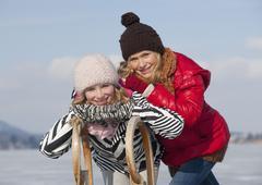 Austria, Teenage girls with sleigh, smiling, portrait - stock photo