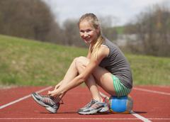 Austria, Teenage girl on track tying her shoelace, portrait Stock Photos