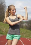 Austria, Teenage girl on track showing her muscles, smiling, portrait - stock photo