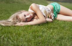 Stock Photo of Austria, Teenage girl lying on meadow, smiling, portrait