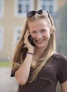Stock Photo of Austria, Teenage girl on mobile phone, smiling, portrait