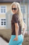 Austria, Teenage girl with hands in pocket, smiling - stock photo