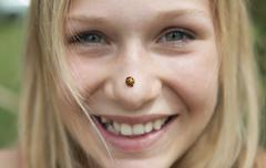 Stock Photo of Austria, Teenage girl with ladybird on her nose, smiling, portrait