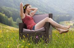 Austria, Young woman sitting on sofa and listening music in field of flowers Stock Photos