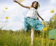 Austria, Young woman running in field of flowers Stock Photos