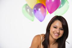 Portrait of young woman with balloons, smiling - stock photo