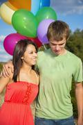 Stock Photo of USA, Texas, Teenage boy and young woman with balloons, smiling