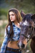 USA, Texas, Cowgirl standing with horse - stock photo