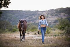 USA, Texas, Cowgirl walking with horse - stock photo