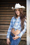 Stock Photo of USA, Texas, Portrait of cowgirl, smiling