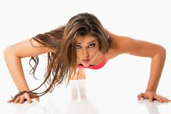 Stock Photo of Young woman doing push ups on white background