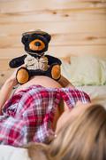 USA, Texas, Pregnant young woman holding teddy bear on belly Stock Photos