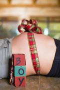 USA, Texas, Ribbon tied in a bow around pregnant belly with letter blocks Stock Photos