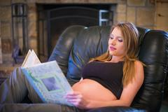 USA, Texas, Pregnant young woman sitting in armchair - stock photo