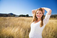 USA, Texas, Raskaana nuori nainen seisoo ruoho, hymyilee, potretti Kuvituskuvat