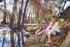 USA, Texas, Husband and wife sitting on creek Stock Photos