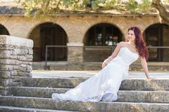 USA, Texas, Young bride in wedding dress posing at historical building - stock photo