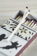 Match box and matchstick with christmas motif on table, close up - stock photo