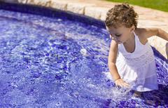 Spain, Baby girl playing in water basin - stock photo