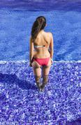 Spain, Teenage girl standing in swimming pool Stock Photos