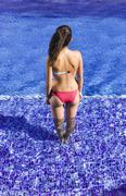 Spain, Teenage girl standing in swimming pool - stock photo