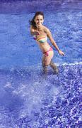 Spain, Teenage girl playing in swimming pool - stock photo
