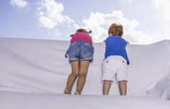 Spain, Boy and girl standing and looking over white couch - stock photo