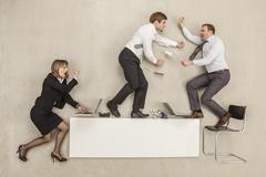 Business people fighting on office desk - stock photo