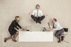 Businessman meditating above office desk while others working - stock photo