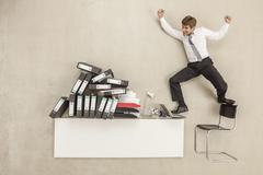 Businessman jumping from office desk and chair besides stack of files - stock photo