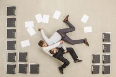 Businessmen fighting in office between files - stock photo