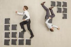 Businessmen stepping on files in opposite direction Stock Photos