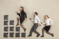 Business people stepping on staircase of files - stock photo