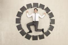 Businessman inside circle of files forming clock Stock Photos