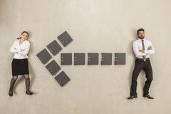 Files forming arrow sign between two business people - stock photo