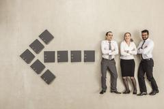 Business people standing along arrow sign formed by files Stock Photos