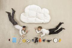 Business people flying between cloud shape pillow and variety of items - stock photo