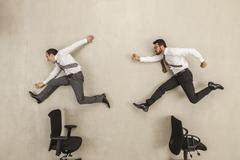 Businessmen chasing against beige background Stock Photos